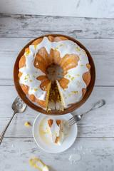 lemon bundt cake with white glaze on cake stand with cake slice