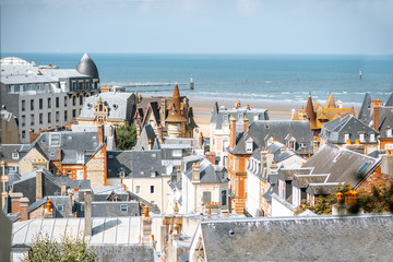 Top view of Trouville city with rooftops of luxury houses and ocean on the background in France
