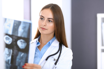 Doctor woman examining x-ray picture while standing near window in hospital. Surgeon or orthopedist at work. Medicine and healthcare concept