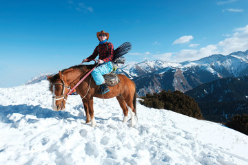 Freeride on horseback. A man in a cowboy hat riding a horse in the snow. Winter. the mountains.