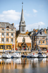 Waterside with ancient buildings and church in Honfleur, famous french town in Normandy