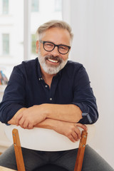 Middle-aged happy bearded man sitting on chair
