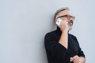 Man smiling with pleasure as he chats on a mobile