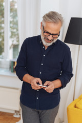 Attractive bearded man smiling as he uses a mobile