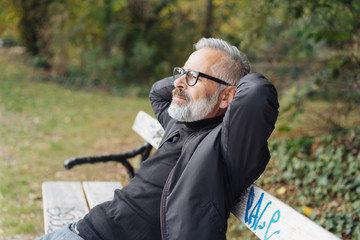 Man relaxing on a park bench with closed eyes