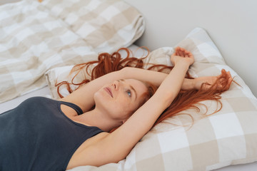 Young woman lying back relaxing on her bed