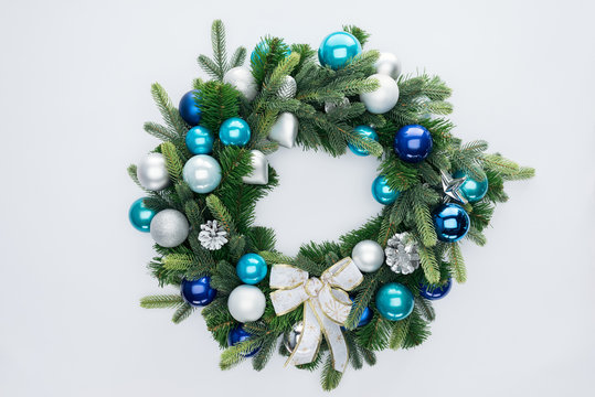 top view of decorative festive wreath with blue and silver christmas toys isolated on white