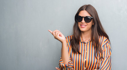 Young brunette woman over grunge grey wall wearing big sunglasses very happy pointing with hand and finger to the side