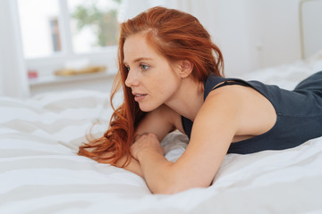 Young redhead woman lying daydreaming