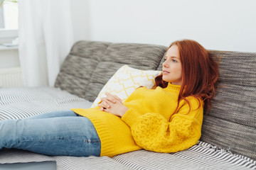 Young woman reclining on a sofa deep in thought