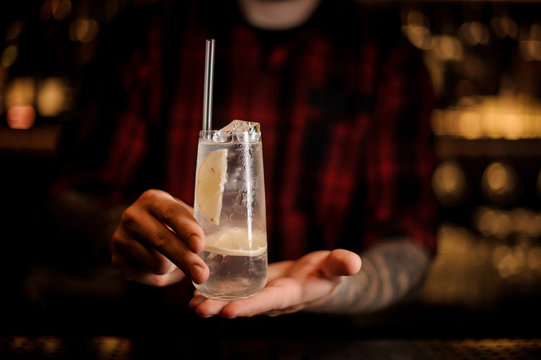 Bartender holding long drink glass filled with Tom Collins cocktail