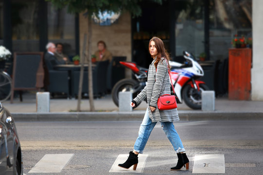 Urban style: Stylish beautiful eastern European young woman crossing street. Beautiful tourist walking on street in Barcelona.