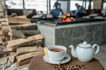 Cup of tea teapot on wood table in restaurant and fireplace is back