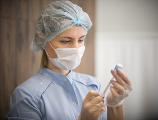 Woman in a cosmetology clinic. The specialist collects the substance in the syringe