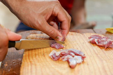 Men's hands cut meat on a cutting board for cooking shish kebab.