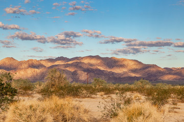 An arid Californian landscape with early morning shadows on mountains