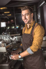 handsome young barista preparing coffee with coffee machine in cafe and looking at camera