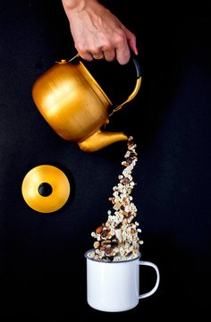 Muesli being poured from a teapot into an enamel mug