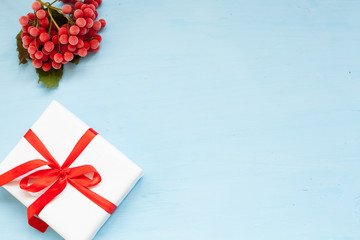 new year's gift and red berries on a blue Christmas background