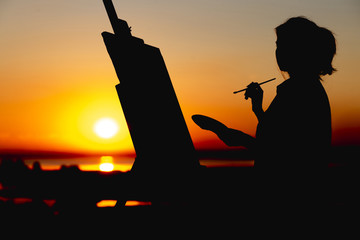 silhouette of a woman painting a picture on canvas on an easel, girl with paint brush and palette engaged in art in a field at sunset