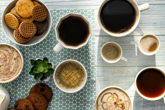 Flat lay composition with cups of tasty aromatic coffee and cookies on wooden background