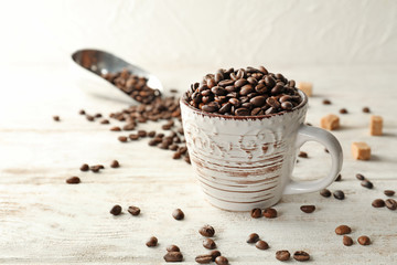 Cup of coffee beans on white wooden table