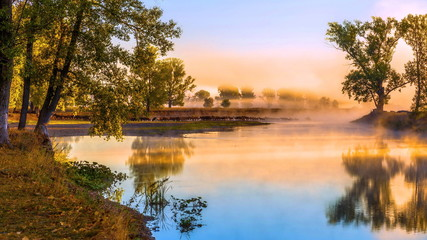 Morning mist on the river at the first rays of the sun.