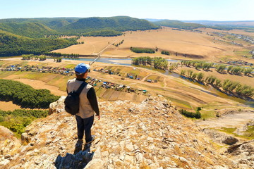 Man Tourist with a backpack is on top of the High Rock Mountain below, the Zilyim River flows against the background of the Ural Mountains. Autumn sunny day.