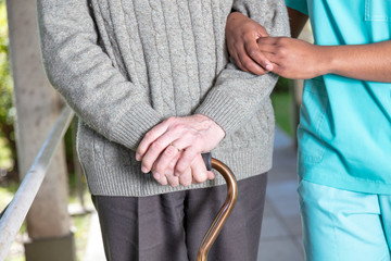 Elderly man with walking stick moving with nurse, detail on the hands