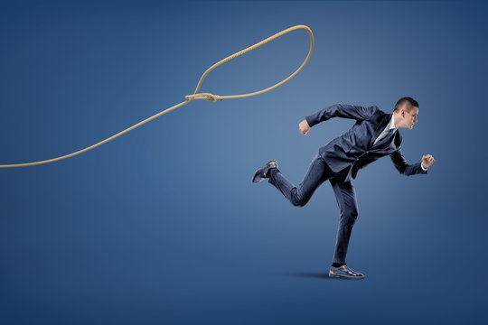 A businessman in a suit runs away from a rope lasso that tries to catch him.