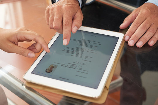 Business people watching resume online on tablet pc at the table