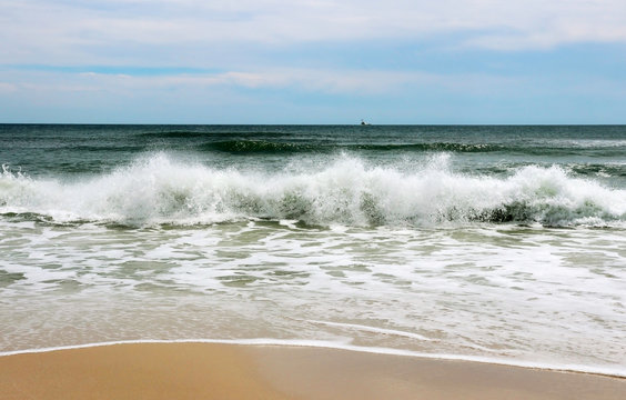 Dreamy beach.Cloudy blue sky over the ocean background.Marine beach landscape with front view of falling waves and sand in a foreground.Gulf of Mexico shore, Alabama, USA.Ocean beach vacation concept.