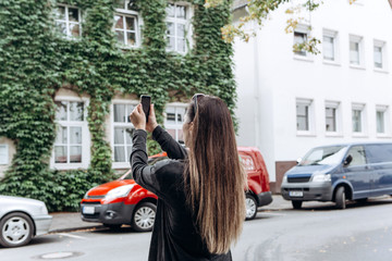 The girl on the street takes pictures of the beautiful buildings in Muenster in Germany. She makes a street mobile photo to share it on social networks with friends.