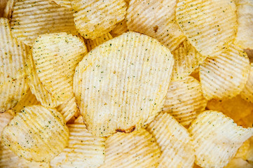 Potato chips corrugated background top view, close-up