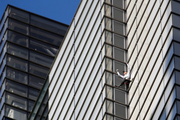 French free-climber Alain Robert, known as 'Spiderman', celebrates as he nears completing his attempt to climb up the outside of the Heron Tower in the financial district of London