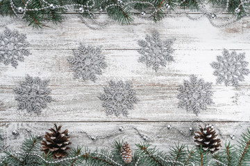 Garlands and snowflakes. Old wooden Christmas background. Fir branches and cones. Xmas greeting card. Top view. Space for your text.