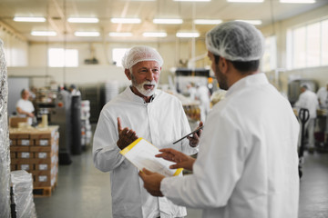 Two serious business man in sterile clothes standing in food factory and talking about business.
