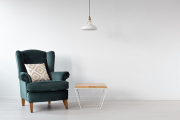 Moss green armchair next to wooden coffee table in white scandinavian interior with copy space on the empty wall