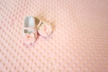 Baby newborn pink background, vintage newborn shoes for baptism on soft texture background , blank space for message