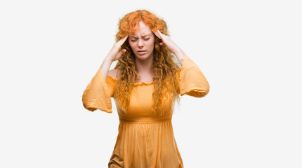Young redhead woman with hand on head for pain in head because stress. Suffering migraine.
