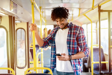 Young modern Afro-American man standing in a public transport and listening to the music.