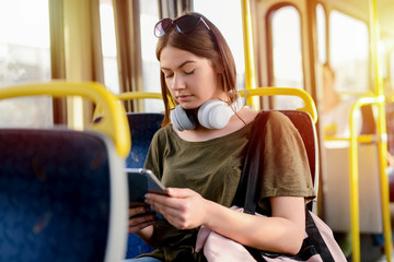 Serious young student girl sitting in a bus and looking at her telephone with serious look. Holding headphones around her neck.