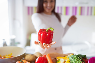 Close up of girl holding red paprika in her hands. Focus is on paprika.