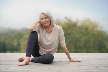 Beautiful elderly woman sitting outdoors in sportswear