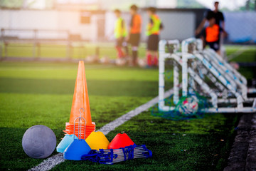 Football and soccer training equipment on green artificial turf with blurry player training background.