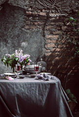 Tablecloth setting with artichokes, flowers and red wine.