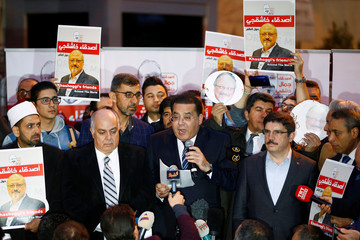 Egyptian politician Ayman Nour talks to the media as friends of Saudi journalist Khashoggi hold posters and banners with his pictures during a demonstration outside the Saudi Arabia consulate in Istanbul