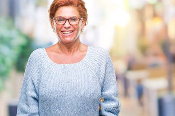 Atrractive senior caucasian redhead woman wearing glasses over isolated background with a happy and cool smile on face. Lucky person.