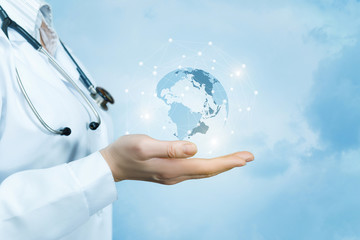 A female doctor with a stethoscope on her neck is holding a crystal, sparkling global map on her hand .