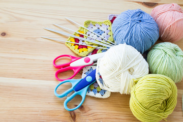 Concept of a woman's hobby. Knitting and work at home. Knitting..Multicolored balls of yarn, scissors, knitting needles, hooks. Materials for creativity and crafts. Copy space.